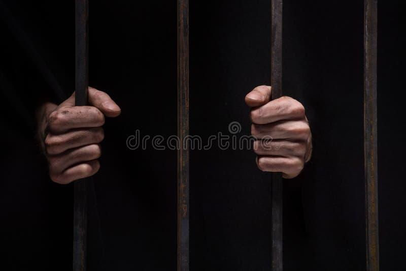 Close-up op handen van mensenzitting in gevangenis stock foto