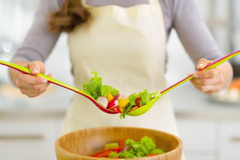 Close-up op huisvrouw die plantaardige salade mengen stock foto