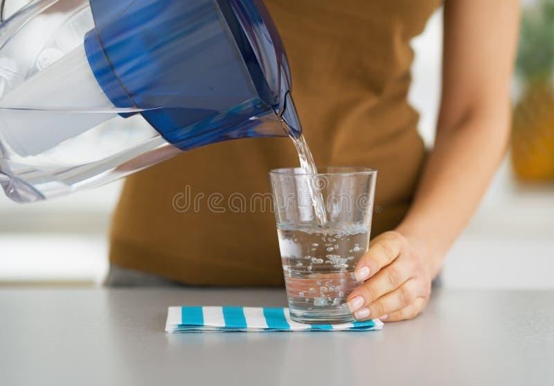 Close-up op huisvrouwen gietend water in glas royalty-vrije stock foto