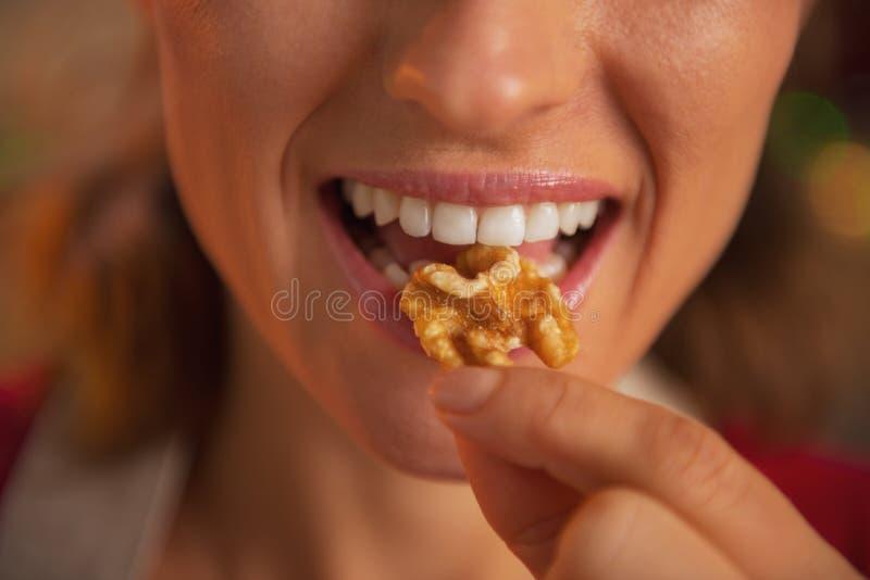 Close-up op jonge huisvrouw die okkernoten eet stock foto's