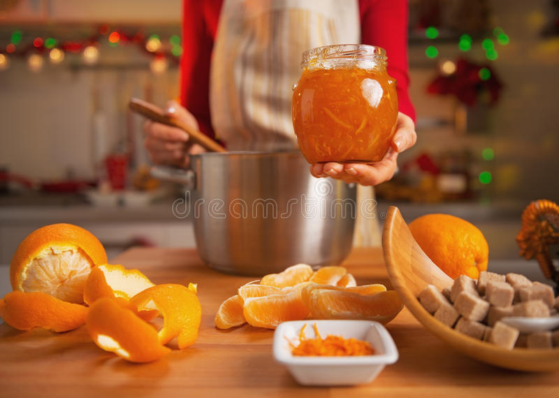 Close-up op jonge huisvrouw die oranje jam in keuken maken royalty-vrije stock foto's