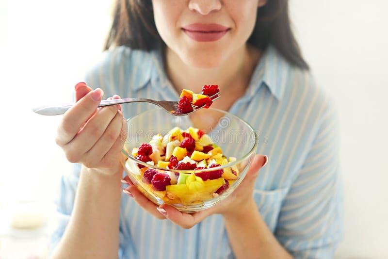 Close-up op jonge huisvrouw die verse fruitsalade eten stock foto's