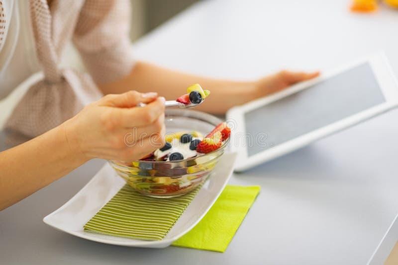 Close-up op jonge vrouw die vruchten salade eten en tabletpc met behulp van royalty-vrije stock foto's