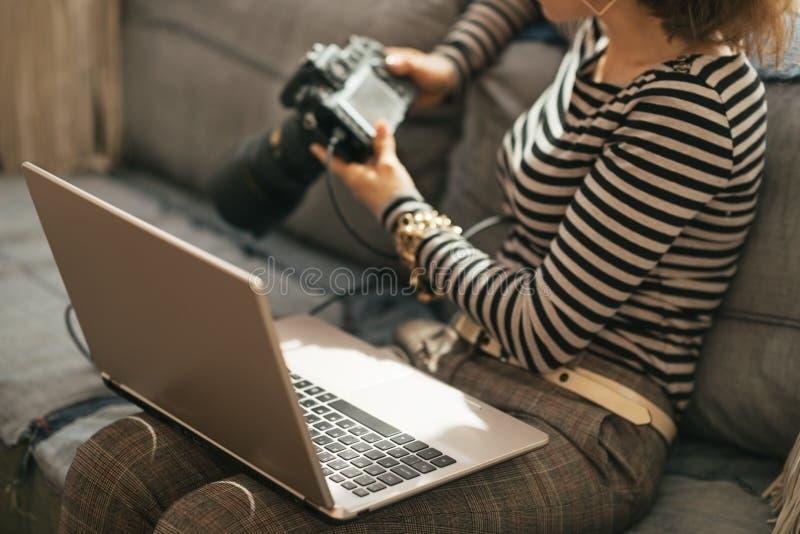 Close-up op jonge vrouw met laptop en dslr camera stock fotografie