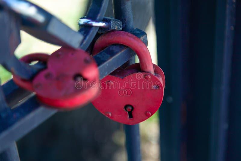 Close-up op sloten van harten in verschillende kleuren en vormen die op de omheining als teken van eeuwige liefde hangen, die tij stock afbeeldingen