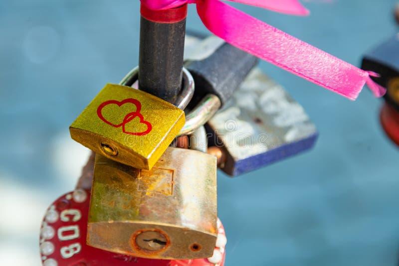 Close-up op sloten van harten in verschillende kleuren en vormen die op de omheining als teken van eeuwige liefde hangen, die tij stock fotografie