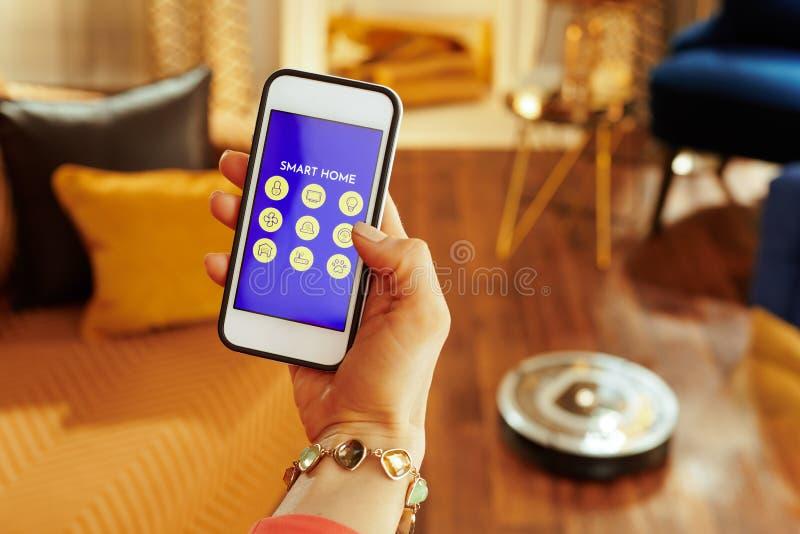 Close-up op telefoon met slim huis app ter beschikking van vrouw en robot royalty-vrije stock fotografie