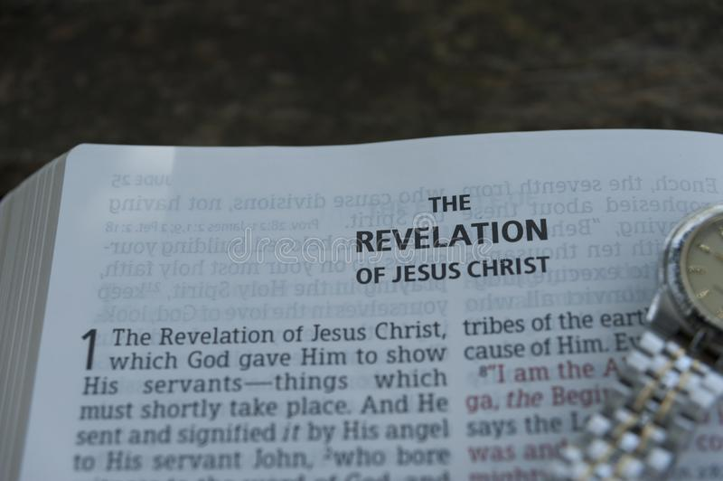 Close-up of open Bible in Revelation of Jesus Christ in chapter 1 with clock. Copy space. Horizontal shot stock images