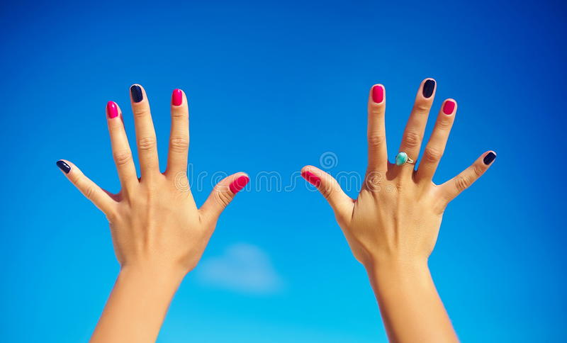 Close up of a open hands with colorful nails stock photography