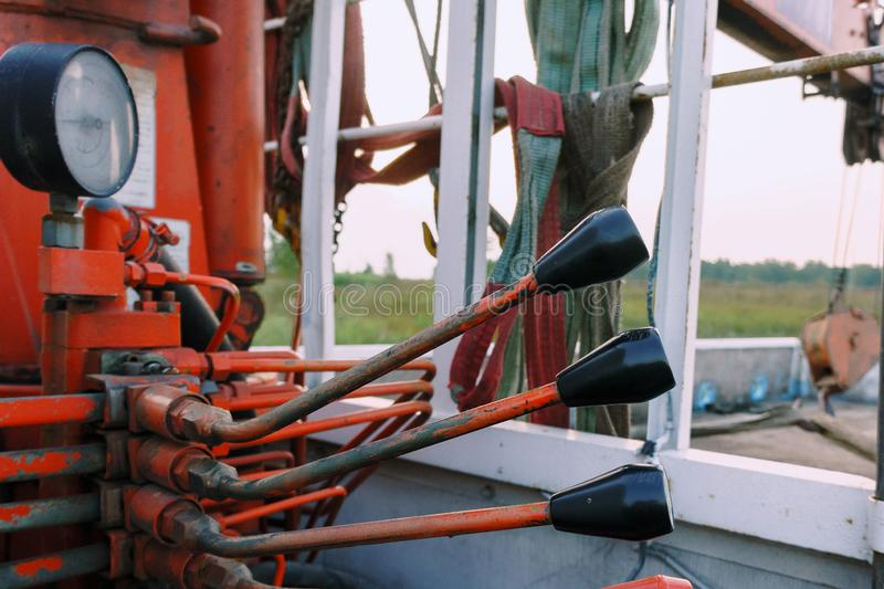 Close-up of operating levers of rusty crane truck hydraulic control system. With measuring device. Bodywork with straps, boom and hook of manipulator in royalty free stock image