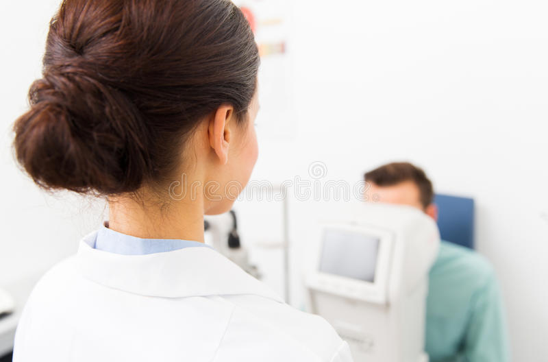 Close up of optician and patient at eye clinic. Health care, medicine, people, eyesight and technology concept - close up of optometrist with autorefractor royalty free stock photo