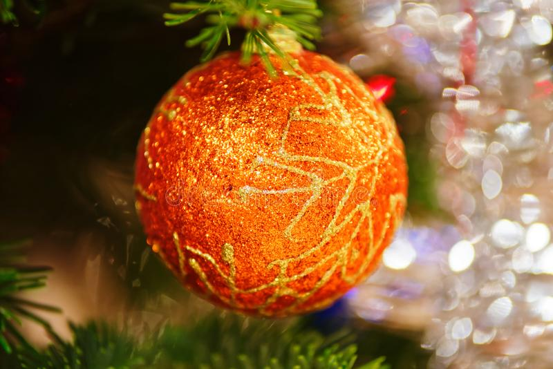 Close-up of an orange christmas ball hanging on fir branch stock images