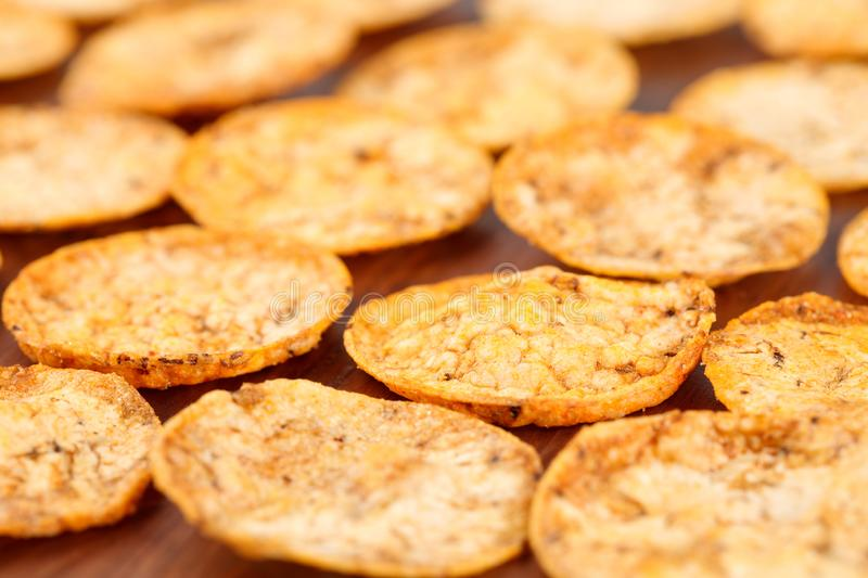 Close up of organic, crispy, baked, whole grain rice chips with tomato and paprika spices. Gluten free healthy snack on a wooden royalty free stock photos