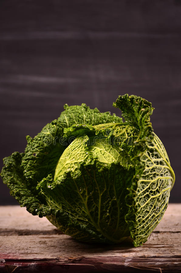 Close up of organic savoy cabbage on the wooden background stock image