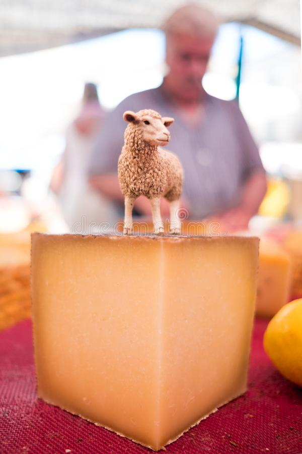 Close up of organic spanish goat cheese piece with goat statuette on it and farmer in background in outdoor street food market on. Spanish goat cheese piece with stock photo