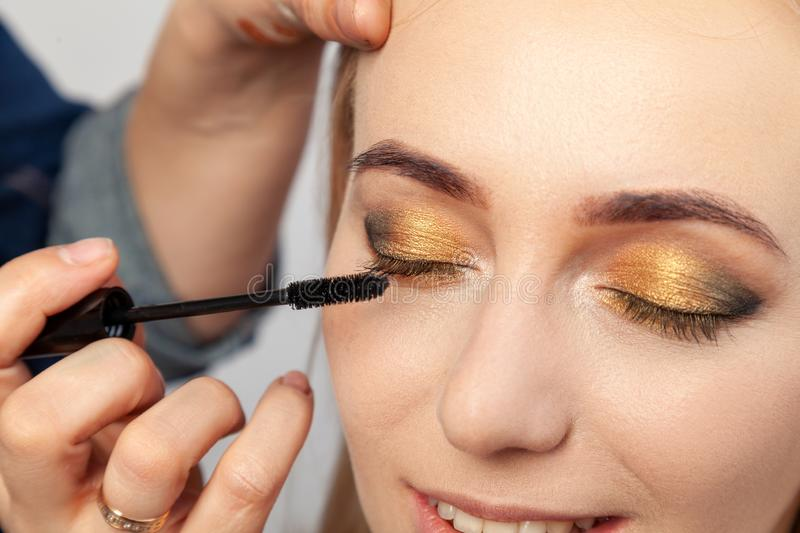 Close-up of an oriental-style eye make-up: golden, brown and green pronounced eye shadows, the make-up artist holds a brush in his stock image