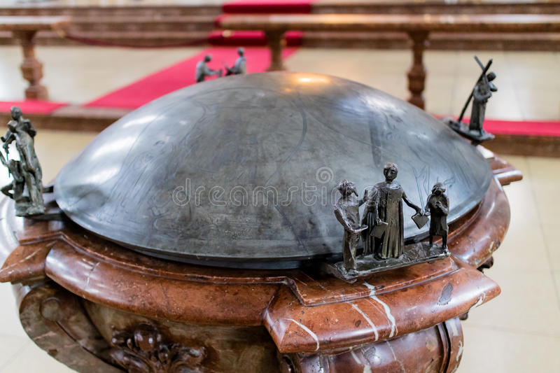 Close up of ornate church fountain with figures. Close up of ornate stone fountain decorated with figures depicting religious scenes near carved wooden railing stock photography