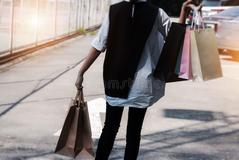 Close up os sacos de compras nas mãos da pessoa shopaholic louca das mulheres no shopping Sacos de compras de papel coloridos imagens de stock royalty free
