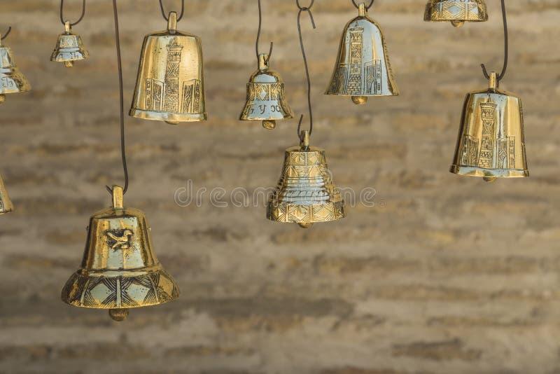 Close up os sinos dourados no fundo borrado do tijolo fotografia de stock