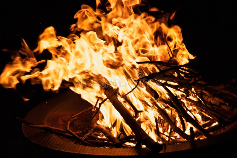 Close up of an outdoor fire pit with a big yellow and orange flames stock images