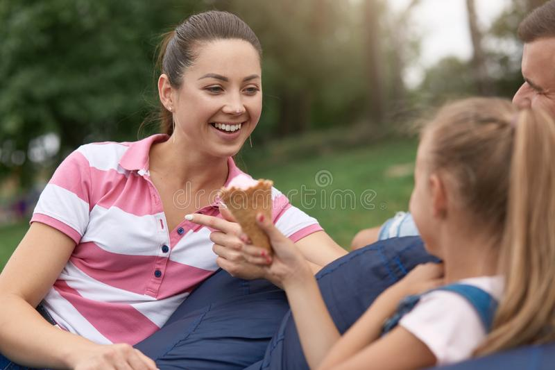 Close up outdoor image of young happy family spending their weekend in park, relaxing while sitting on frameless chair, daughter stock photos