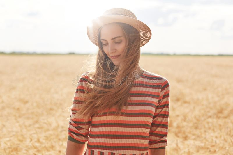Close up outdoor portrait of beautiful woman in straw hat and striped shirt, female posing in meadow, looks smiling down and royalty free stock photos