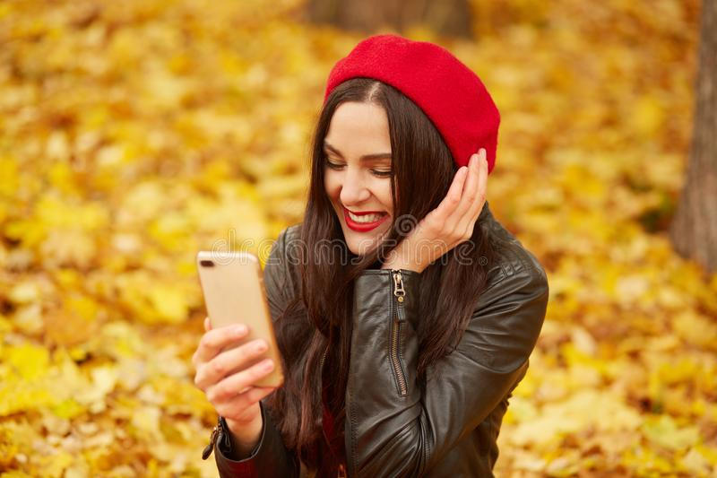 Close up outdoor portrait of woman, lady looks happy and taking self picture via smartphone in autumn park, young model posing on royalty free stock photo