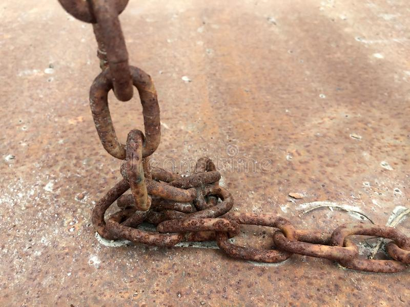 Close up outdoor view dirty ground and brown color, of an ancient rusty chain placed on the ground. royalty free stock photography