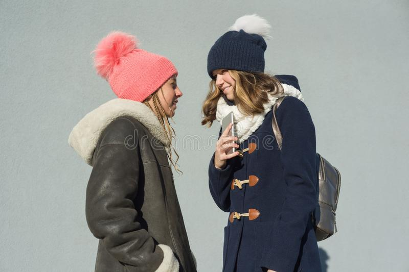 Close-up of an outdoor winter portrait of two teenage girls students in a profile smiling and talking royalty free stock image