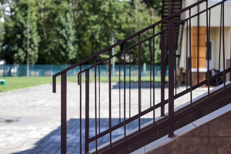 Close-up outdoors detail of short stone staircase with metal protective simple primitive metal fence and handrails on lit by brigh. T summer sun big yard and royalty free stock image
