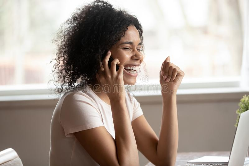 Overjoyed biracial woman laugh talking on cellphone stock photo