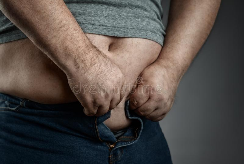 Close up of overweight man trying to wear small jeans stock photography
