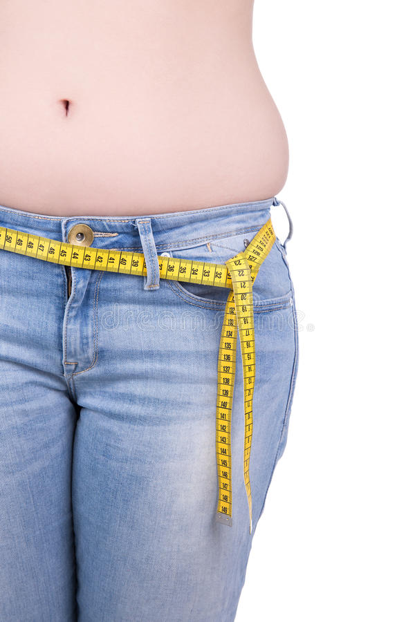 Close up of overweight woman's belly and measure tape isolated o royalty free stock image