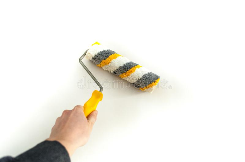 Close up of painter arm painting a wall with paint roller. Hand with paintbrush roller isolated on white. stock photos