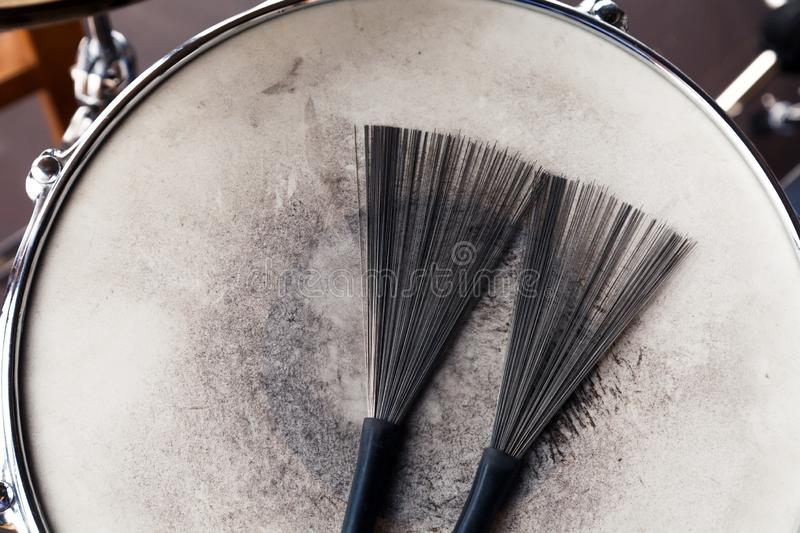 Close-up of a pair of black drum brushes on a white shabby drum. Concept concert, live music, performance, musical evening in a royalty free stock images