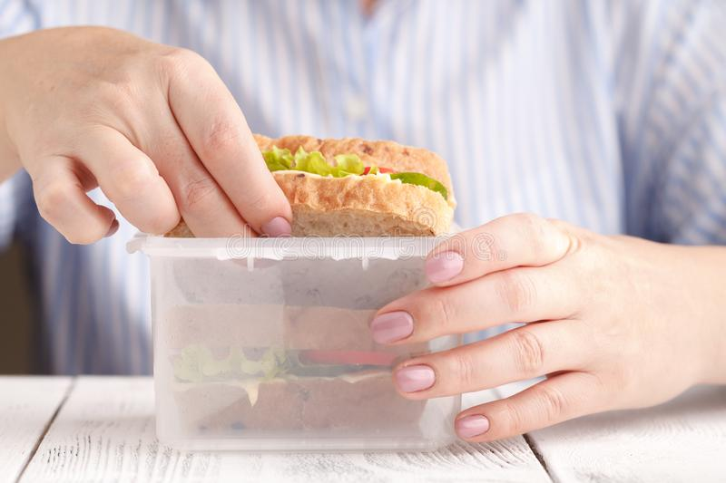 Close up on pair of female hands removing a healthy wholesome wholemeal bread ham sandwich from her lunch box during lunch break royalty free stock photo
