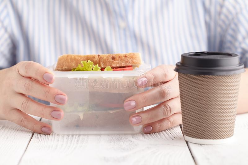 Close up on pair of female hands removing a healthy wholesome wholemeal bread ham sandwich from her lunch box during lunch break stock image