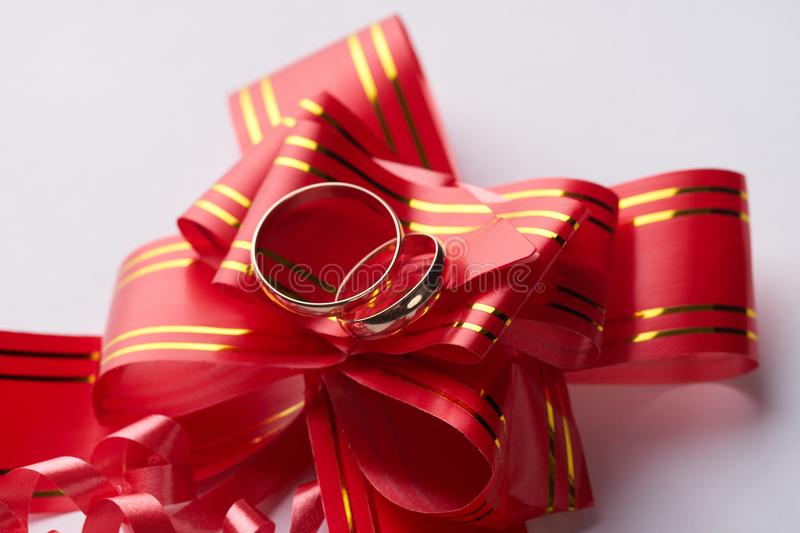 Close-up of pair Gold Wedding rings on red wedding ribbon bow stock image