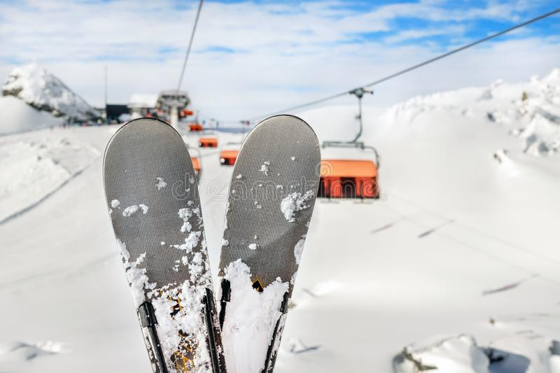 Close-up pair of skis on mountain winter resort with ski-lift and beautiful winter mountain panoramic scenic view.  stock photography