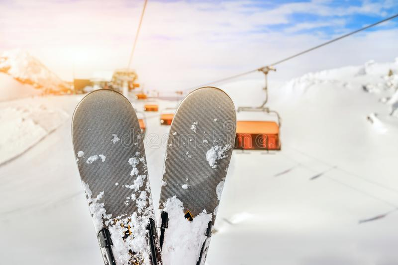 Close-up pair of skis on mountain winter resort with ski-lift and beautiful winter mountain panoramic scenic view. Sport, snow, nature, landscape, season, sky stock images