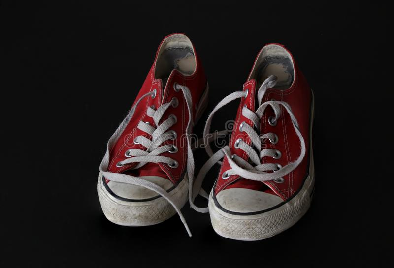 Close up of pair of sneakers - red and white vintage worn out shoes - youth hipster shoes on black background - top view stock photos