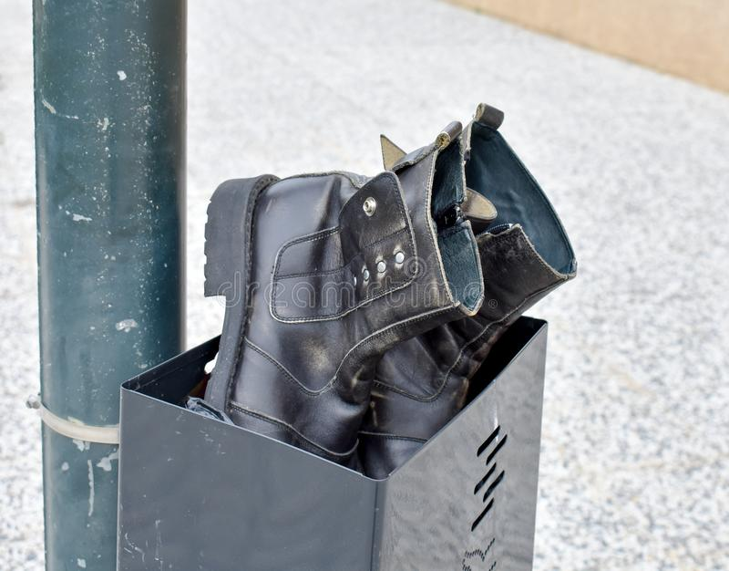 a pair of used black boots made in black leather abandoned in a black bin. Boots and bin at a post in the sidewalk of the street. royalty free stock images