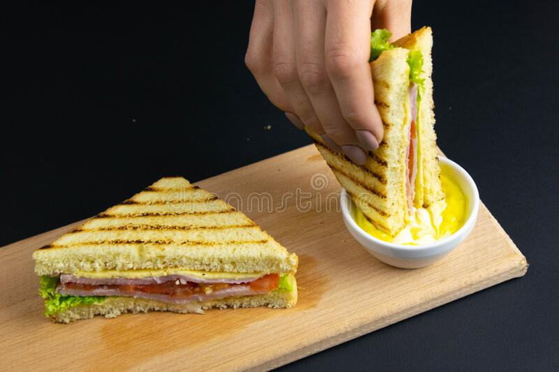Close up on pair of young girl`s hands removing a healthy wholesome wholemeal bread ham sandwich royalty free stock images