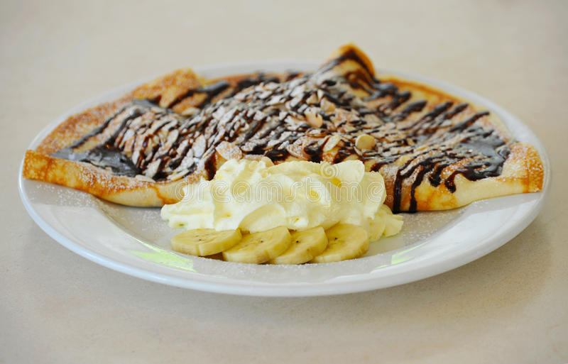 Close-up pancakes with bananas and chocolate. On white plate royalty free stock photo