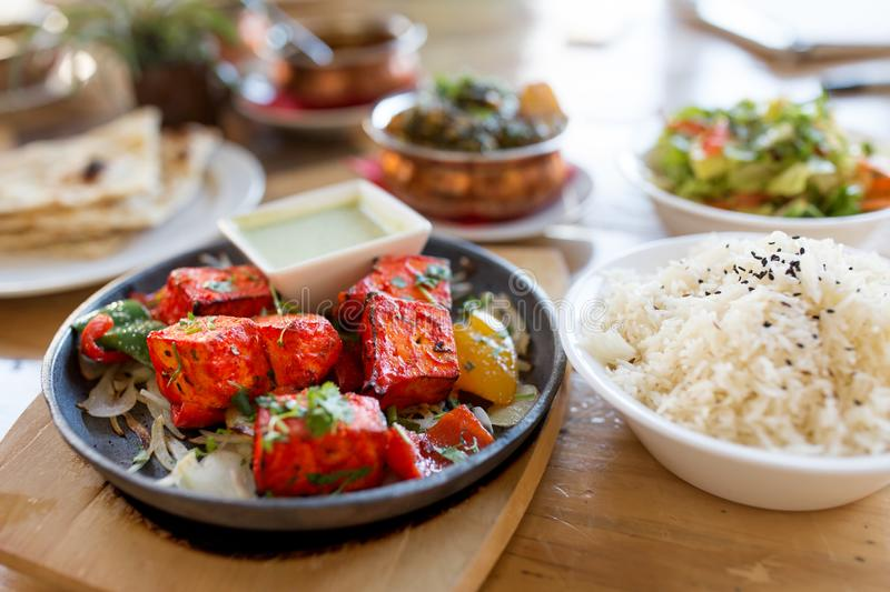 Close up of paneer tikka dish with sauce on table. Food, south asian cuisine, culinary and cooking concept - close up of paneer tikka chunks with bowl of dip royalty free stock images