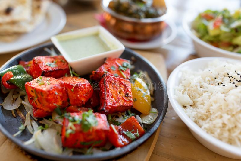 Close up of paneer tikka dish with sauce on table. Food, south asian cuisine, culinary and cooking concept - close up of paneer tikka chunks with bowl of dip royalty free stock photo
