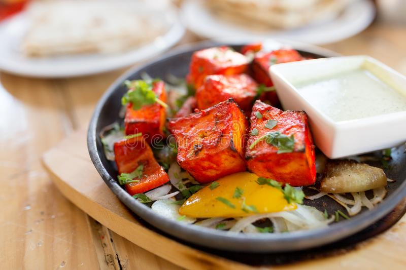 Close up of paneer tikka dish with sauce on table. Food, south asian cuisine, culinary and cooking concept - close up of paneer tikka chunks with bowl of dip royalty free stock photography