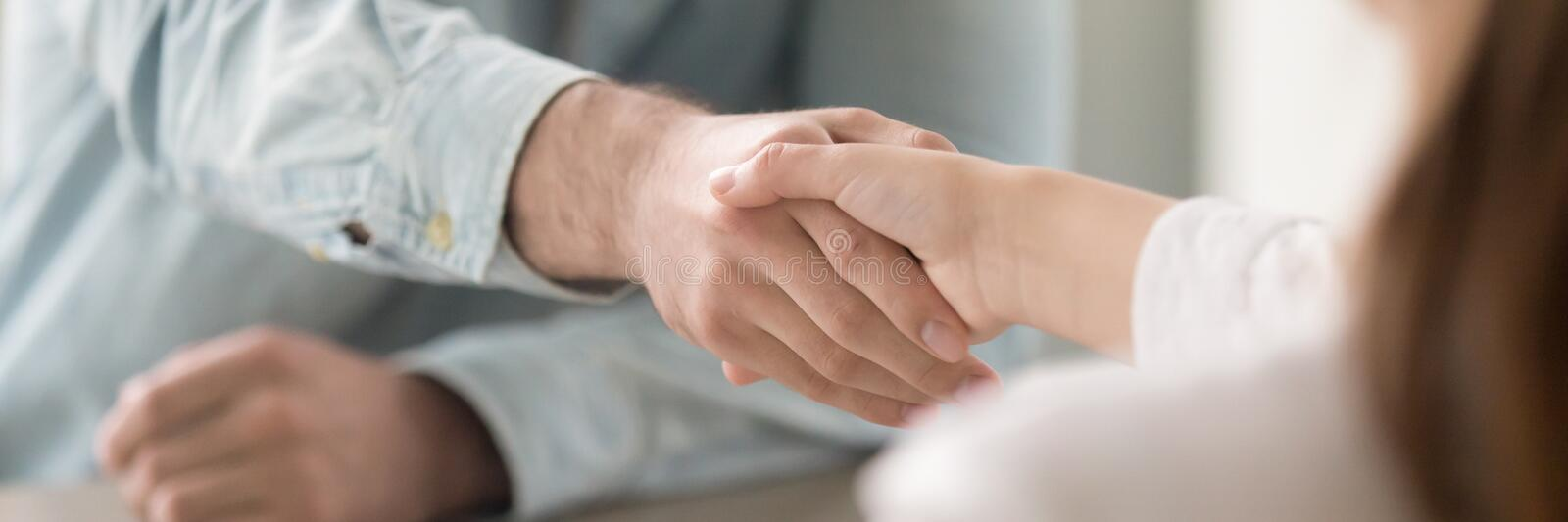 Close up panoramic image businesswoman and businessman shaking hands stock photo