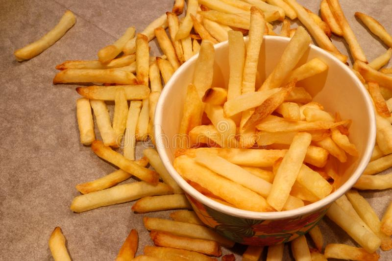 Close up on a paper cup with crispy golden French fries. royalty free stock photo