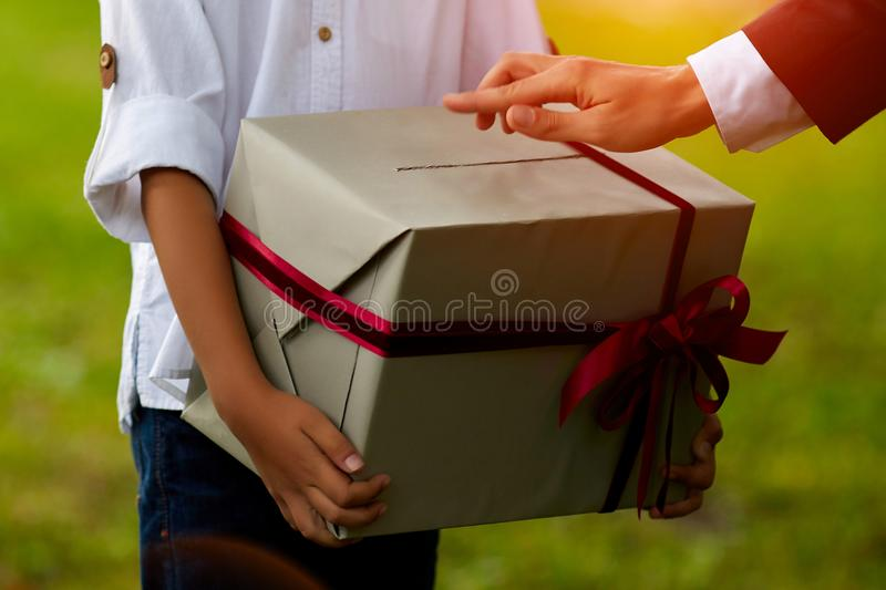 Close-up young asian man holding a christmas red gift box on sofa and christmas tree background at home stock photography